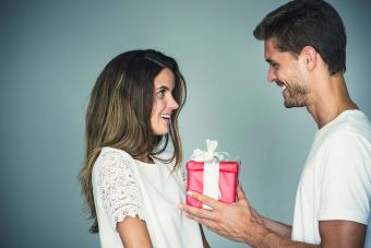 Man surprising his girlfriend with a gift