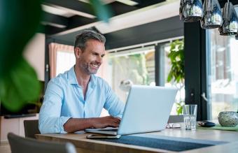 Mature man at home using a laptop