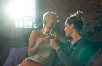 couple sitting in sofa, toasting wine