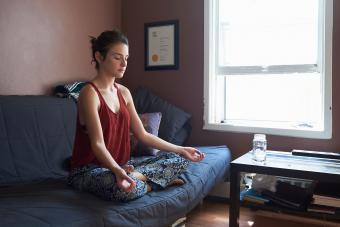 Woman meditating on sofa