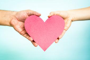 Two hands holding a big and red love heart shape, on blue background