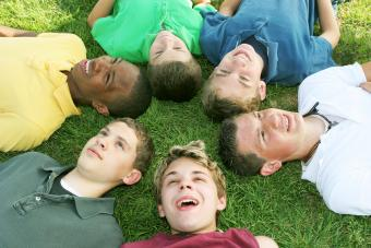 Boys lying on the grass in a circle