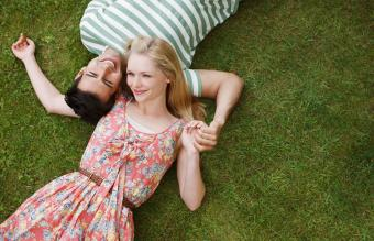 Couple laying in grass and holding hands