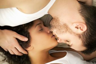 Young couple lying on their bed and kissing