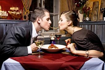 Couple Sharing Single Strand of Pasta at Dinner