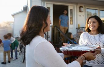 woman delivering casserole to friend