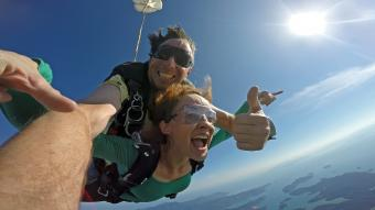 Woman tandem skydiving with instructor