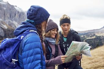 Three young women hiking in the mountains looking at map