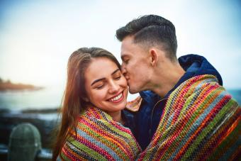 Happy young couple covering themselves with a blanket outdoors