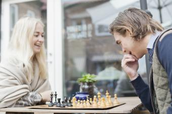 Happy couple playing chess at outdoor cafe