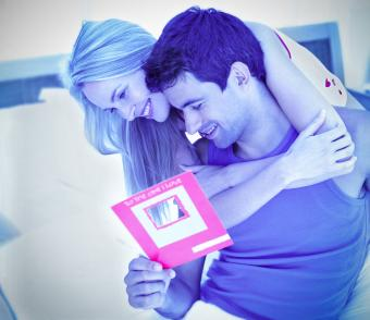 young couple reading a card and hugging on a bed