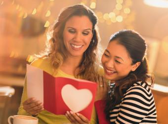 Affectionate lesbian couple with Valentines Day card