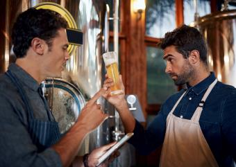 Two men at a brewing inspecting a beer