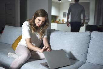 Young woman sitting on sofa in evening, peeking at boyfriend's laptop