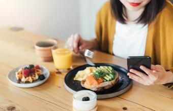 woman using smartphone while having breakfast