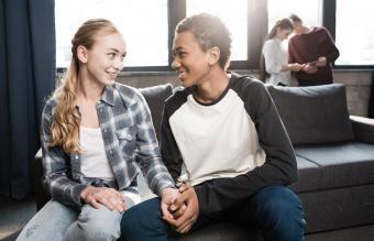 Happy teenage couple sitting on sofa