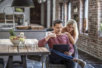 Happy couple siting in country house kitchen, looking at laptop