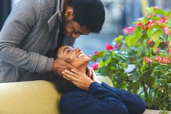 Man staying behind woman and touching her face while smiling