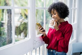 Smiling woman with cup of coffee and cell phone standing