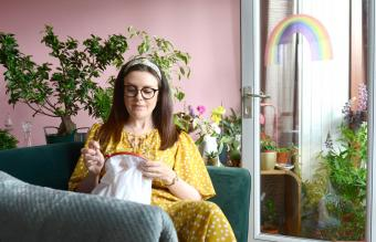 Lady embroidering a rainbow