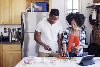 Happy man cutting tomatoes while standing with girlfriend at home