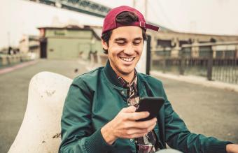 smiling young man using cell phone