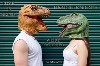 Couple wearing dinosaur mask against green shutter