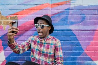 man taking selfie near colorful wall