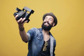 Bearded young man in studio taking selfie with instant camera