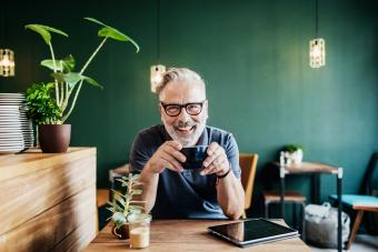 Cafe Customer Smiling While Drinking Coffee
