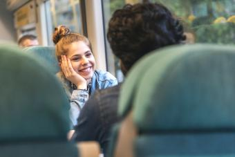 Happy young woman traveling by train and smiling