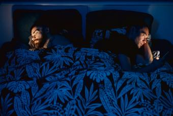 couple in bed under the sheets turning back on each other and looking at phones