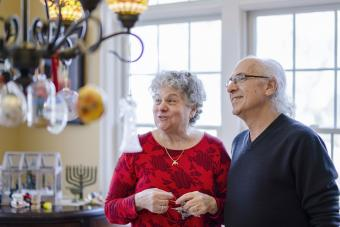 Senior couple decorating their house for the winter holidays, both Christmas and Hanukkah
