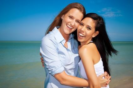 Photo of a lesbian couple embracing at the beach