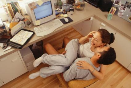 Couple embracing in front of computer