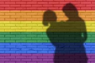 Shadow of couple on rainbow wall