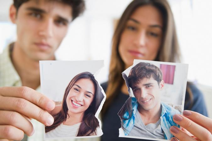 Couple holding torn photo after breaking up