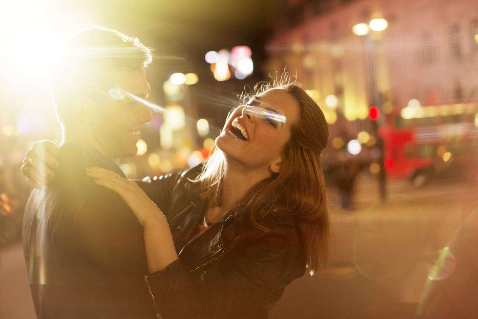 Couple hugging in the street at night