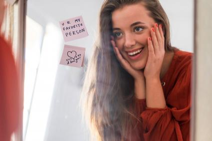 Woman finding love notes on mirror