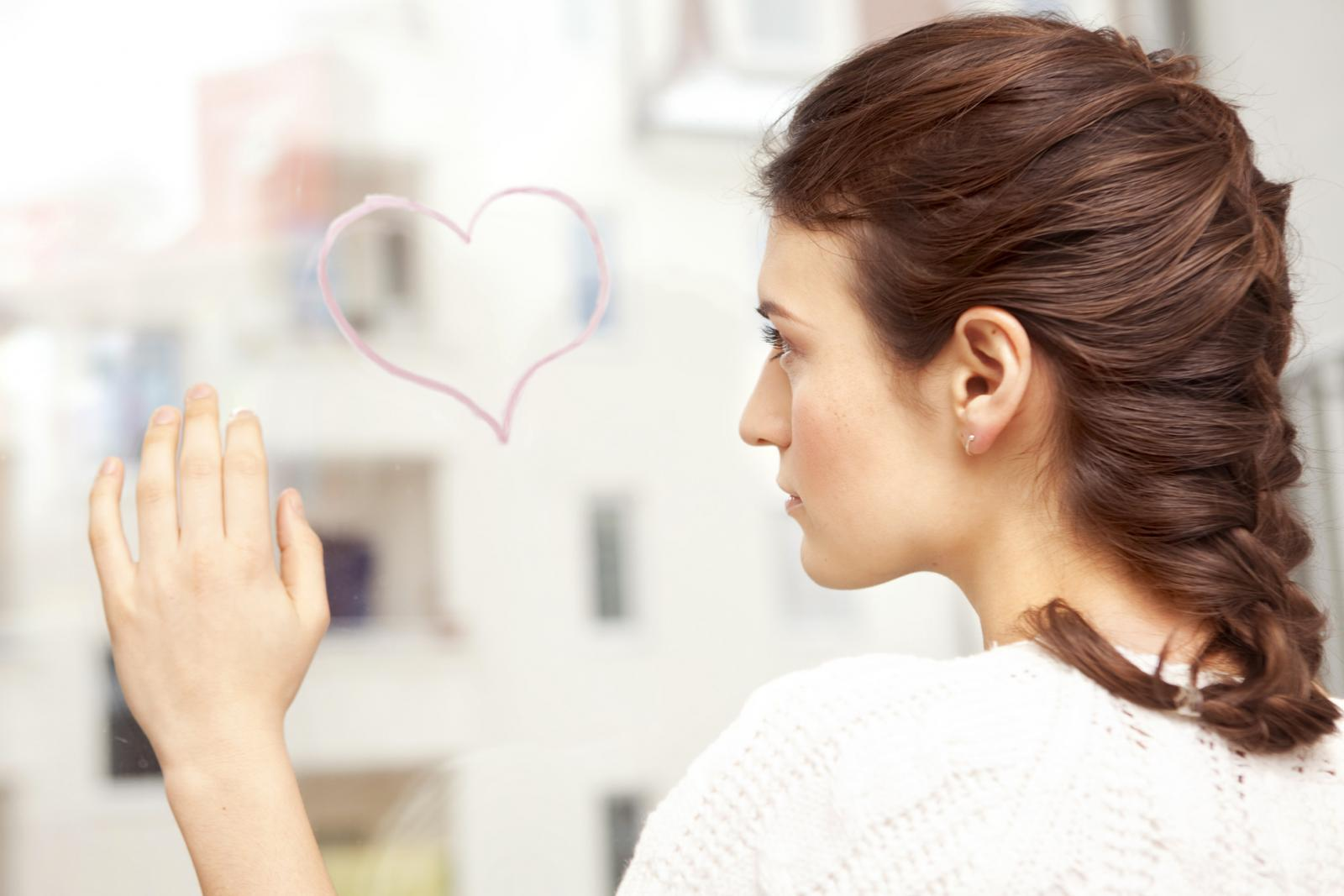 Woman looking sadly at a painted heart