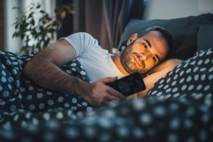 Smiling man texting in bed