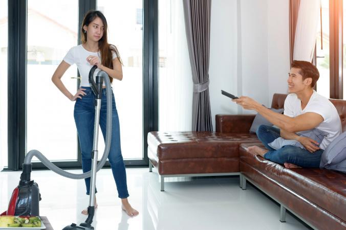 Woman vacuuming and husband watching media