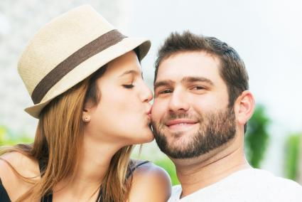 Woman giving her boyfriend a kiss on the cheek