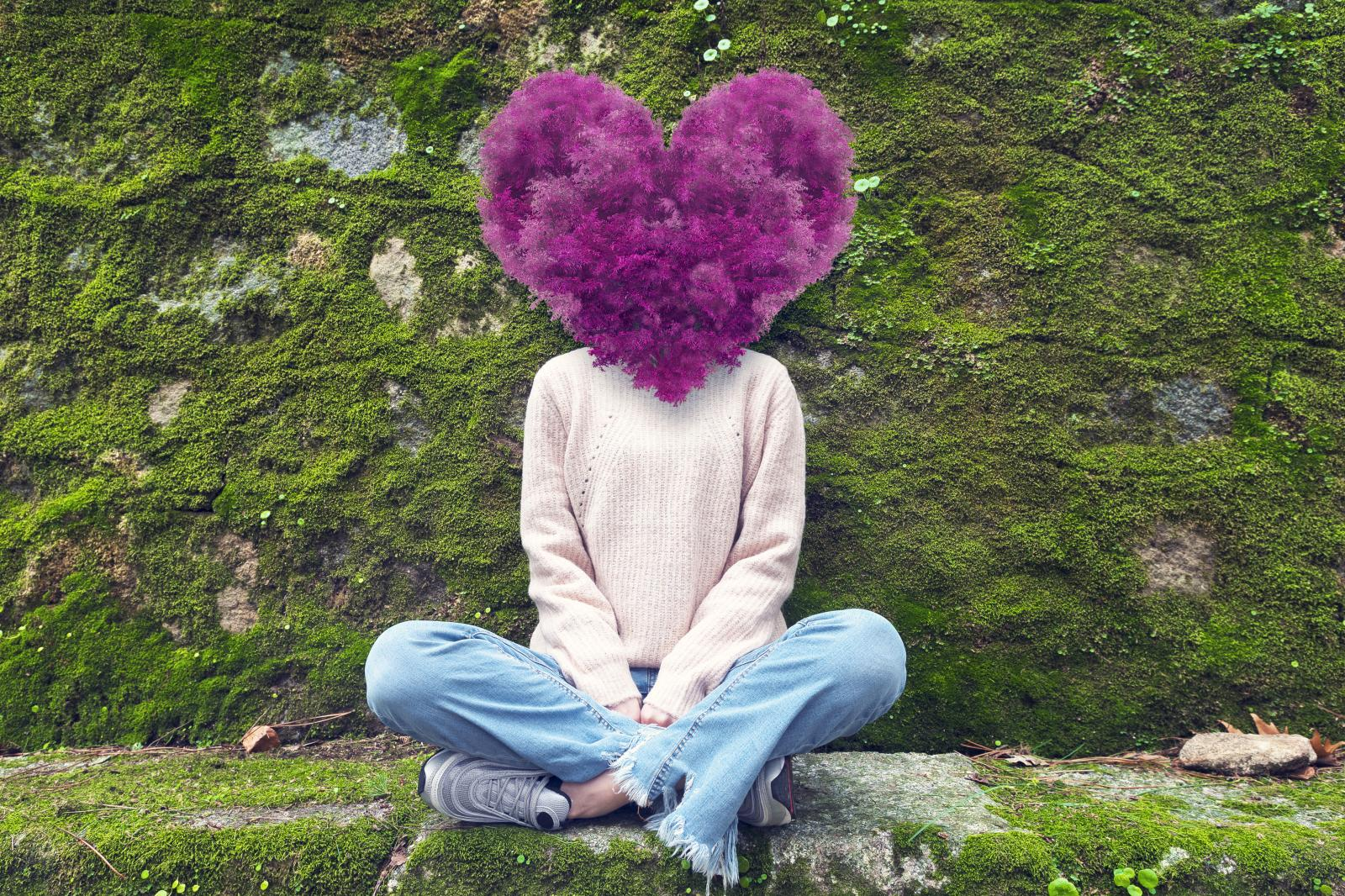 Woman with purple heart-shaped tree over face, sitting on a stone bench