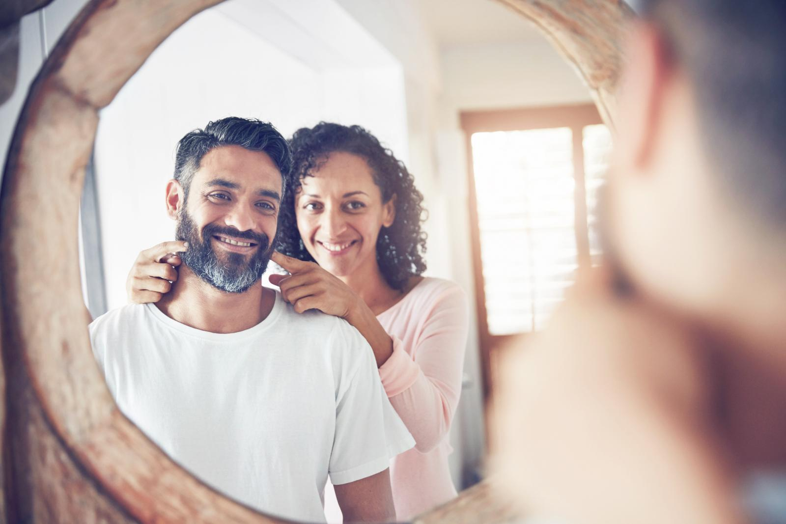 Shot of a mature man looking at his reflection in the mirror with his wife encouraging him to smile