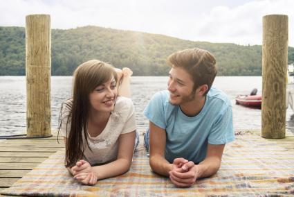 Young couple lying on blanket on lakeside
