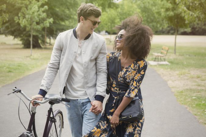 affectionate couple with bike holding hands
