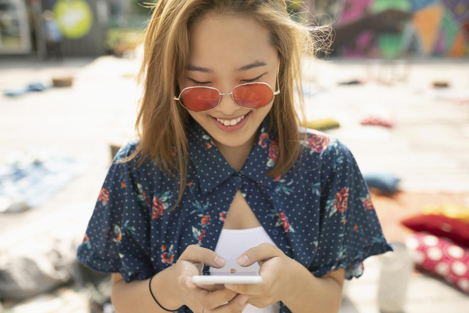Teenage girl with sunglasses using smart phone