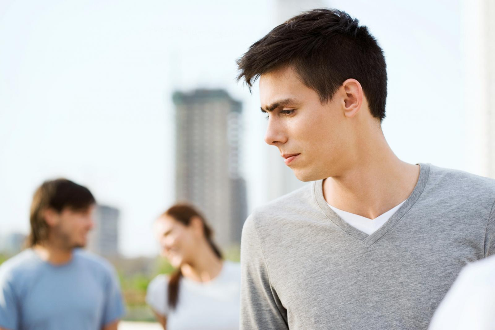 Young man looking to the side, young couple in background