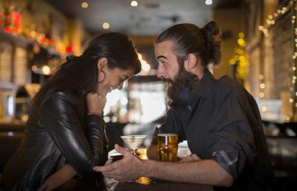 Couple talking at table with cocktail and beer